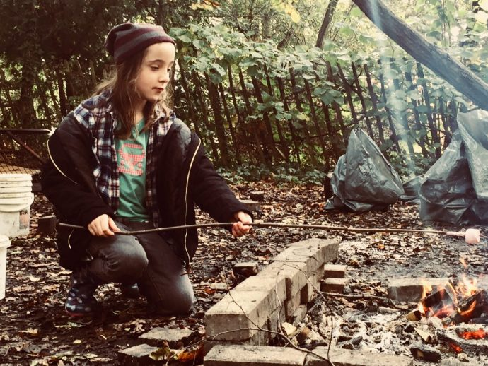 Child toasting marshmallows over a campfire.