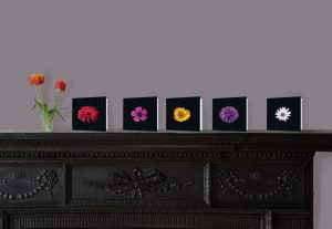Floral greetings cards on display on a fireplace.
