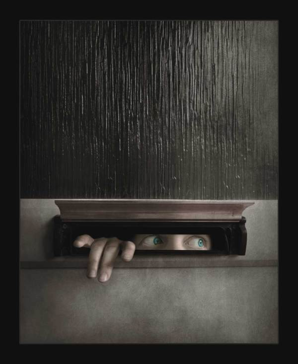 weird fine art created during the 2020 lockdown as part of my lockdown series. The image shows a person peaking out from a letter box.