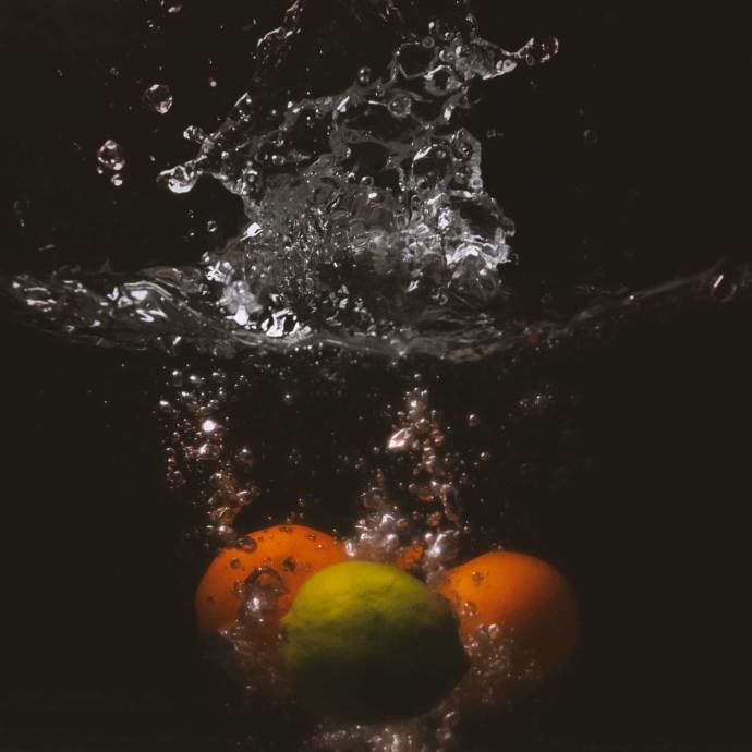 oranges and a lime creating a water splash