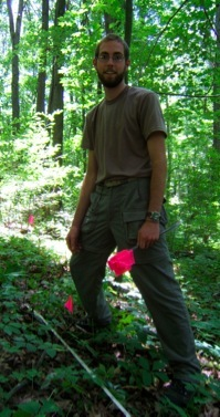 Colin, standing in the woods with flags