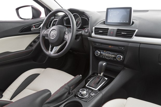 Interior shot of 2014 Mazda 3 with shot of door. Clearly shows door handle and manual lock.