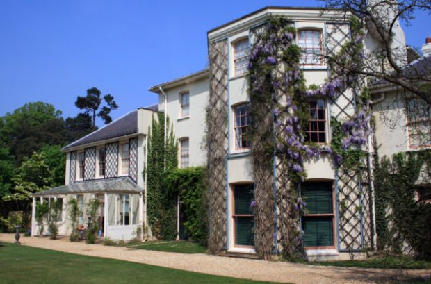 Darwin's home from the side, white with flowering purple vines growing on lattices attached to the walls