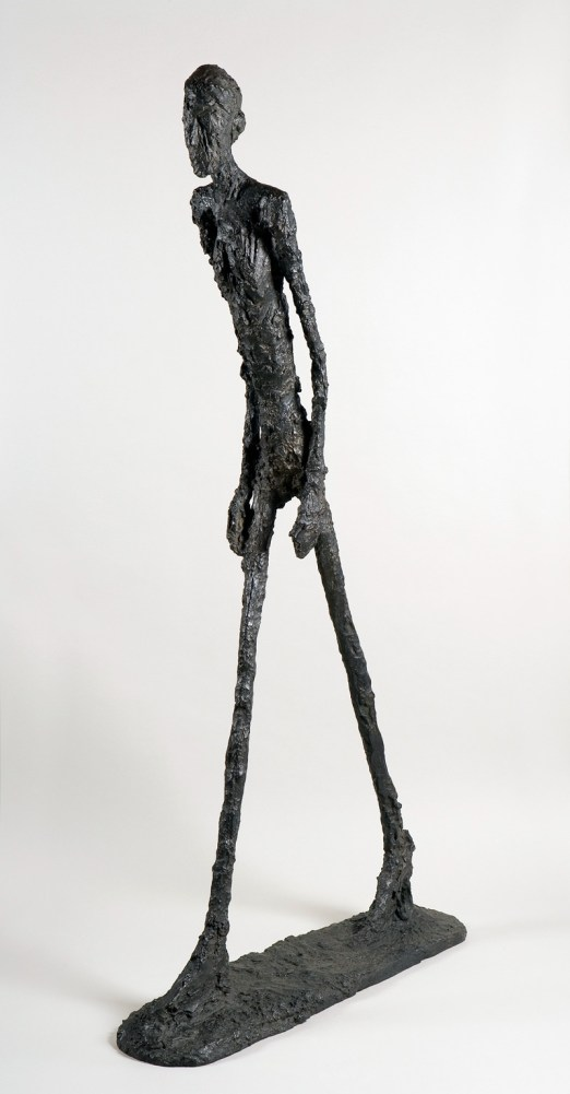 "Alberto Giacometti's ""Man Walking"" Sculpture. Thin and elongated figure with a rough surface leaning forward with one foot in front of the other in a walking posture"