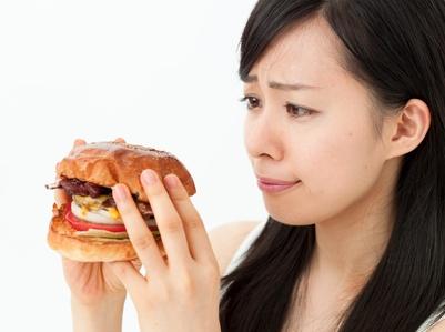 ハンバーガーを食べようとして考える女の子