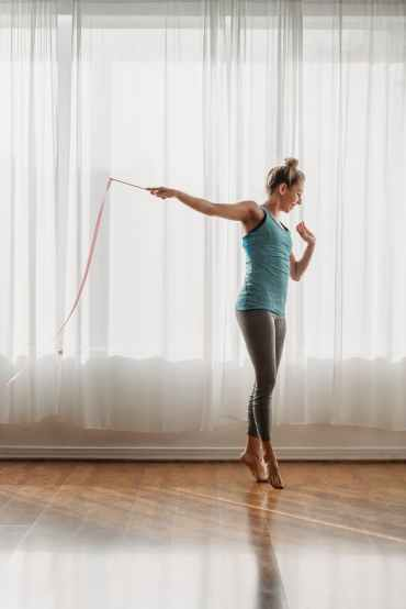 graceful young female gymnast performing dance with ribbon in studio