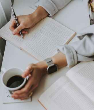 person writing on notebook while holding coffee mug