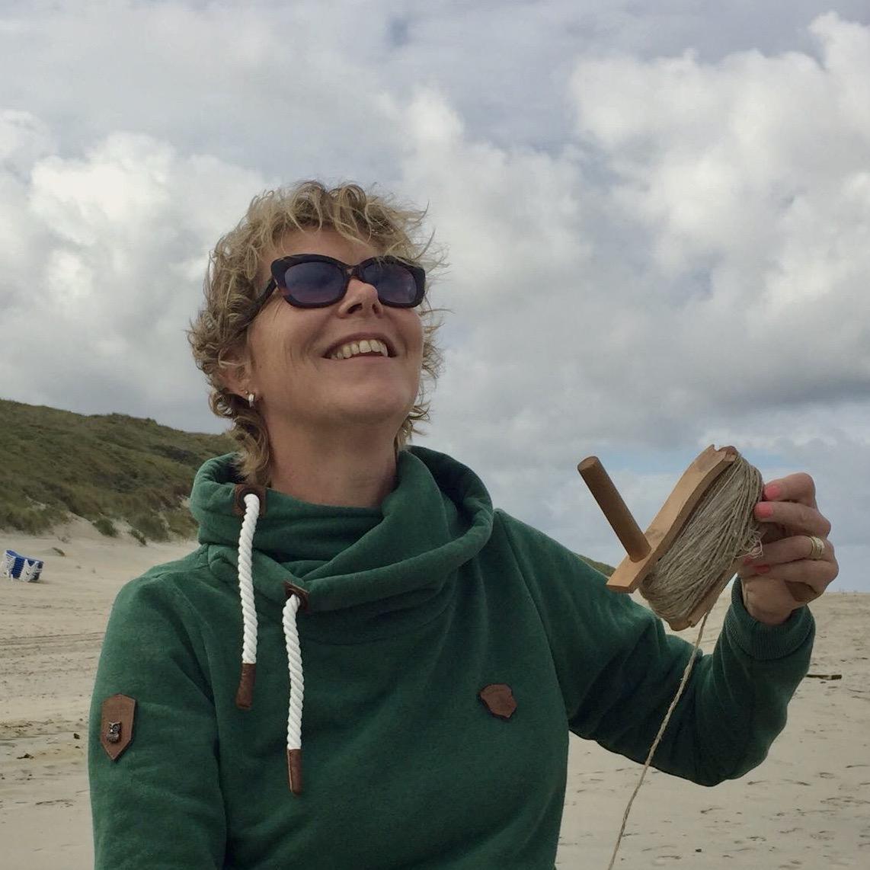 dame kijkt omhoog naar vlieger, met vliegertouw in de hand. sas doet ook mee.nl