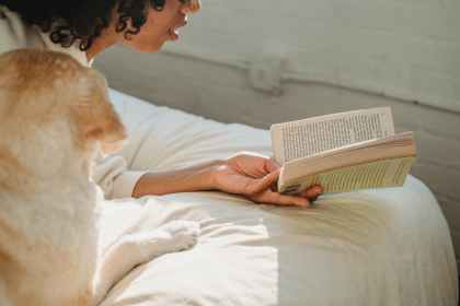 woman reading a book in bed with her dog