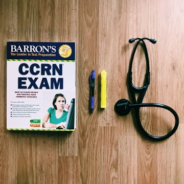 CCRN study book and stethoscope on wood