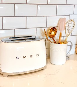 rustic glam girly kitchen with le creuset and white smeg toaster, gold whisk