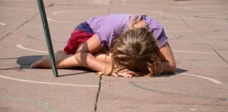 Little girl lying down on road all alone