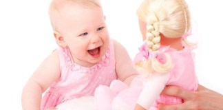 Cute little girl cheerfully looks at a baby toy