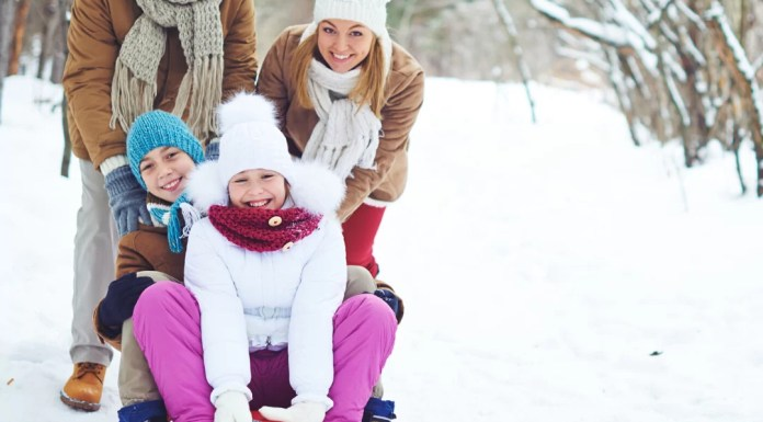 Parents playing with kids in snow