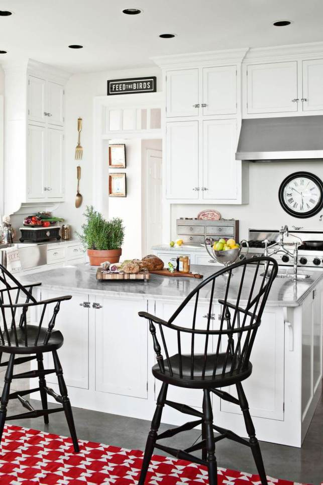 Windsor stools and a red-patterned carpet sit in front of the kitchen's island
