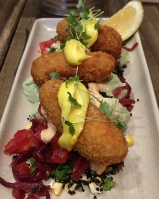 Goat cheese croquettes accompanied by black quinoa, mustard, and tomato.