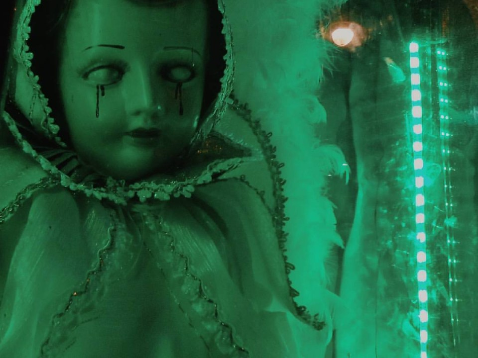 dark image of a doll dressed in christening clothes with blood tears