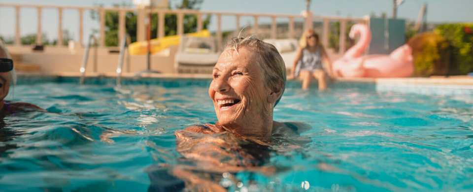 A happy and laughing senior woman swimming in a swimming pool.