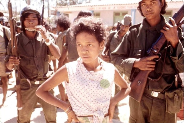 Elemen sipil dan bersenjata selama kudeta UDT di bulan Agustus 1975, nampak seorang perempuan dengan tulisan di dada berbunyi: