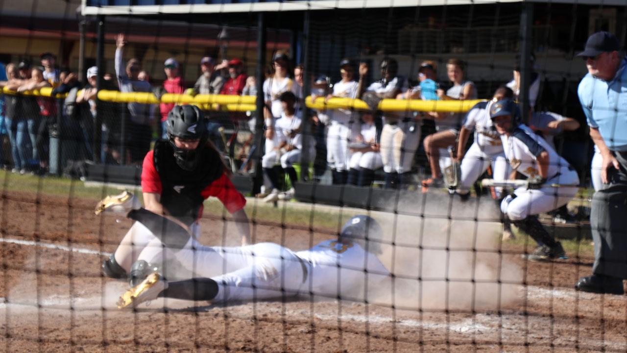 softball player sliding home