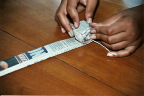 2. Lay a 4-inch piece of string across the end of the strip, letting a half an inch or more stick out from either side. Roll the strip tightly around the string. Add more strips until your coil of paper is the right size to fit inside the tuna can. Press the coil down inside, making the surface as even as possible. Be sure the string wick projects from the center. The tighter the coil, the longer it will burn.