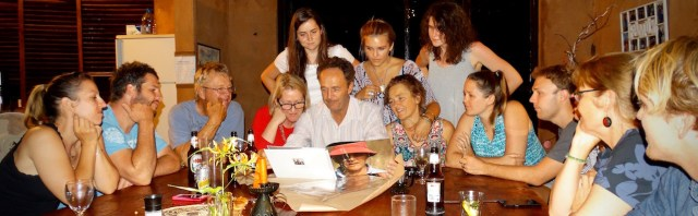 Chris looking at the book Dee made for him, surrounded by his family.