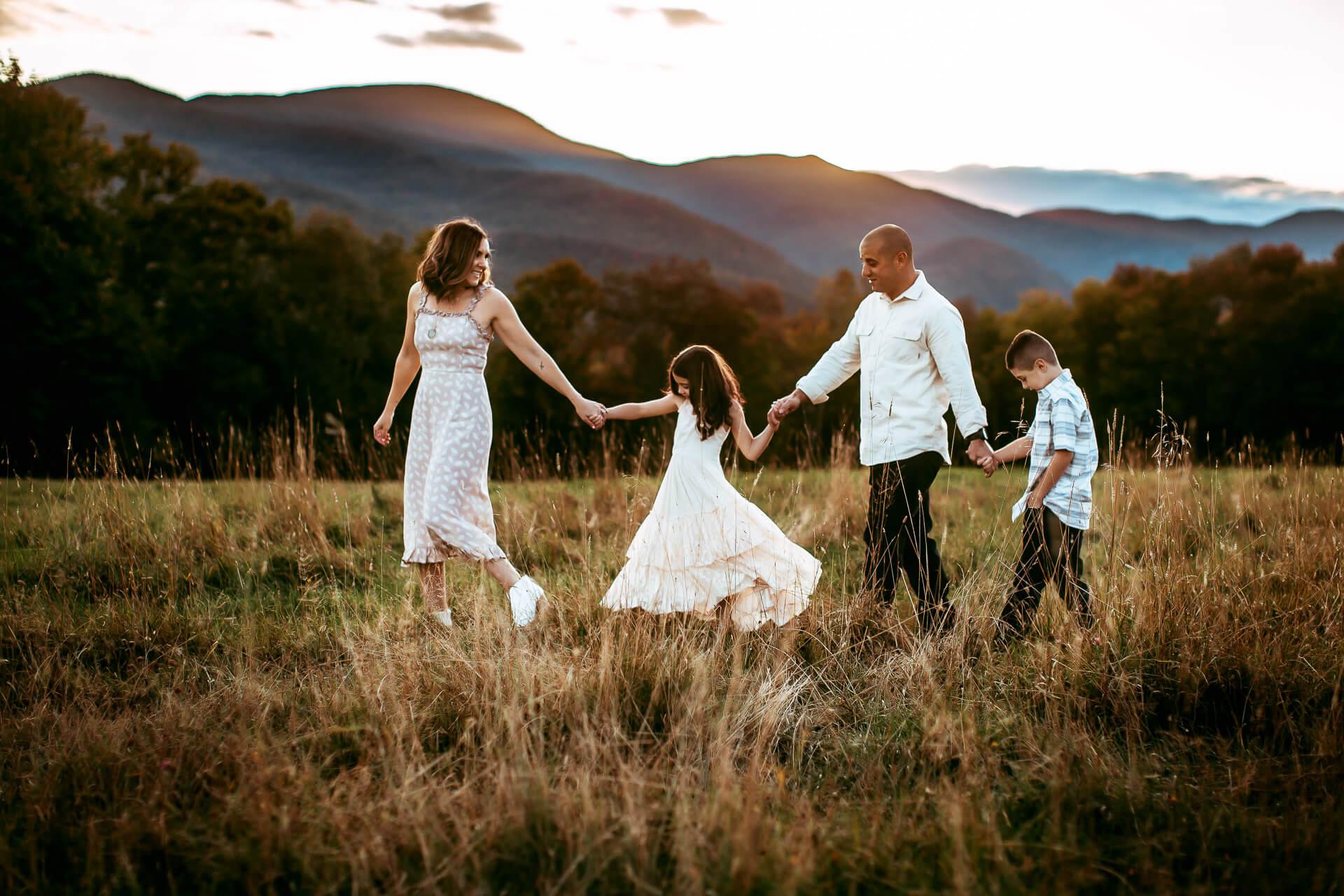 Family walking through field at sunset