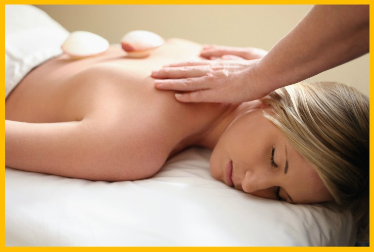 Woman laying on white sheets receiving a massage