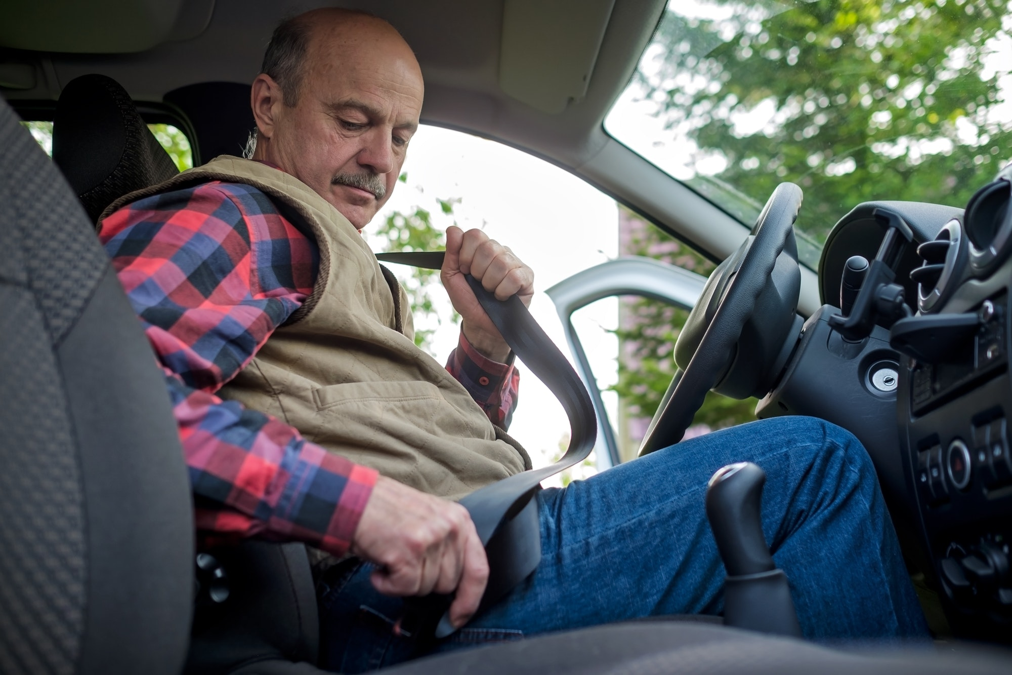 Mature man fastening seat belt in car