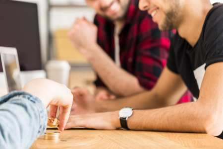 Cropped photo of friends sitting at a table and playing with gol