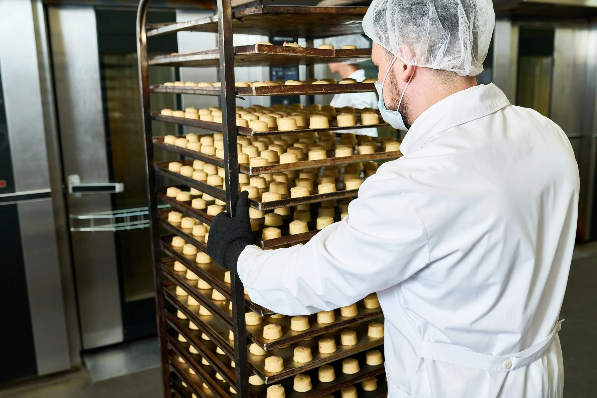 Confectionery factory worker pushing trays rack with pastry