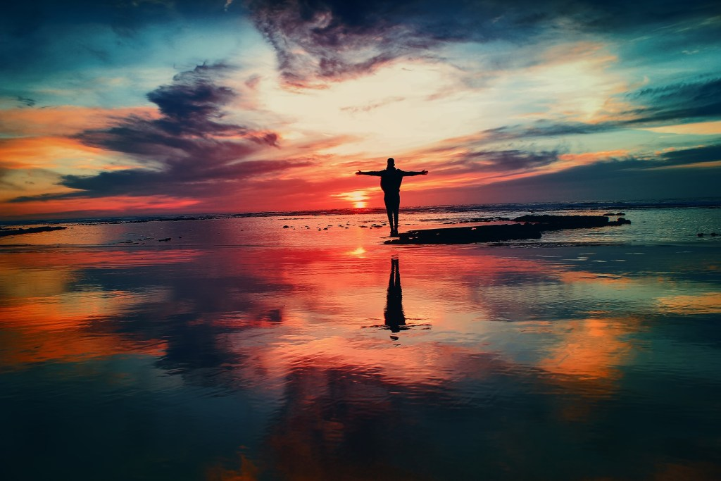 image of a person standing in the pool of water and welcoming the sunrise