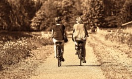 two women riding the bicycles along the countryside road