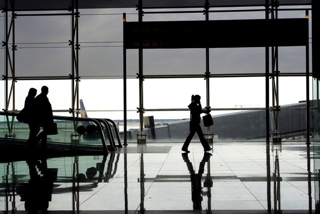 a woman walking along tall glass windows of airport