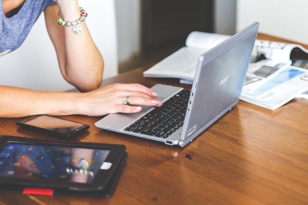 woman sitting at the table and working on her laptop computer
