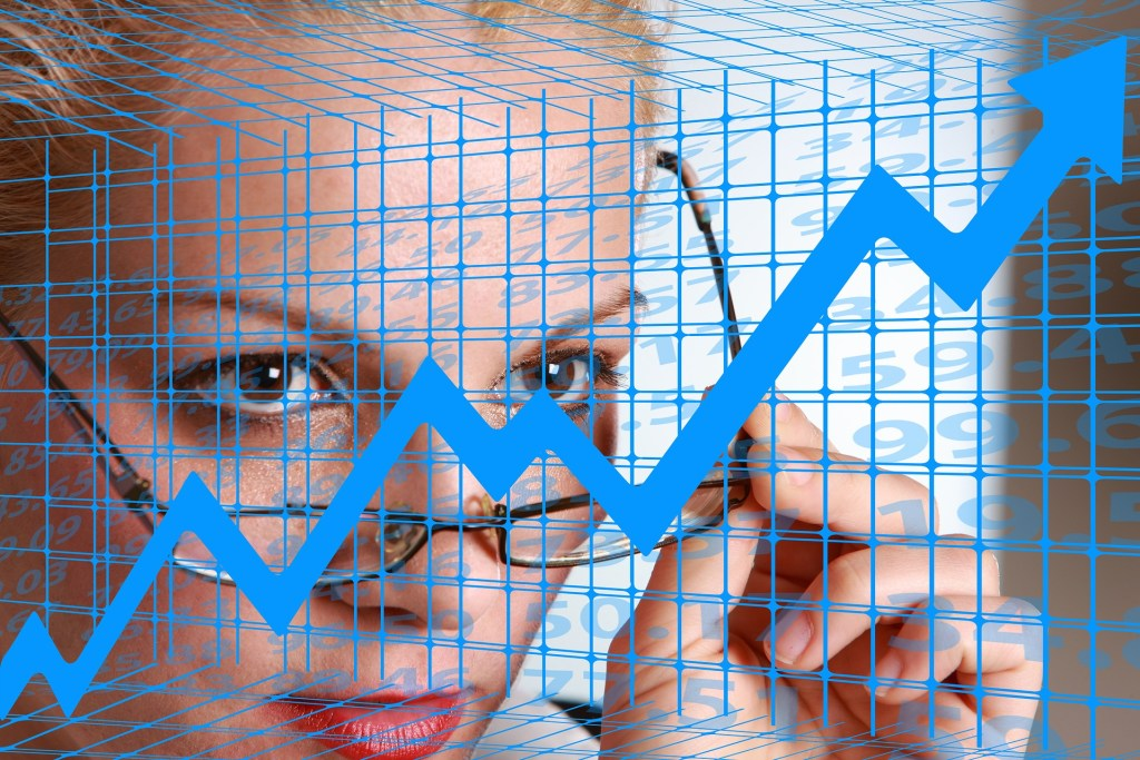 a woman is looking at the glass marker board with stock market chart