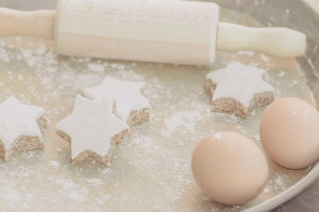 table with eggs, baking dough and cookies - holiday budget