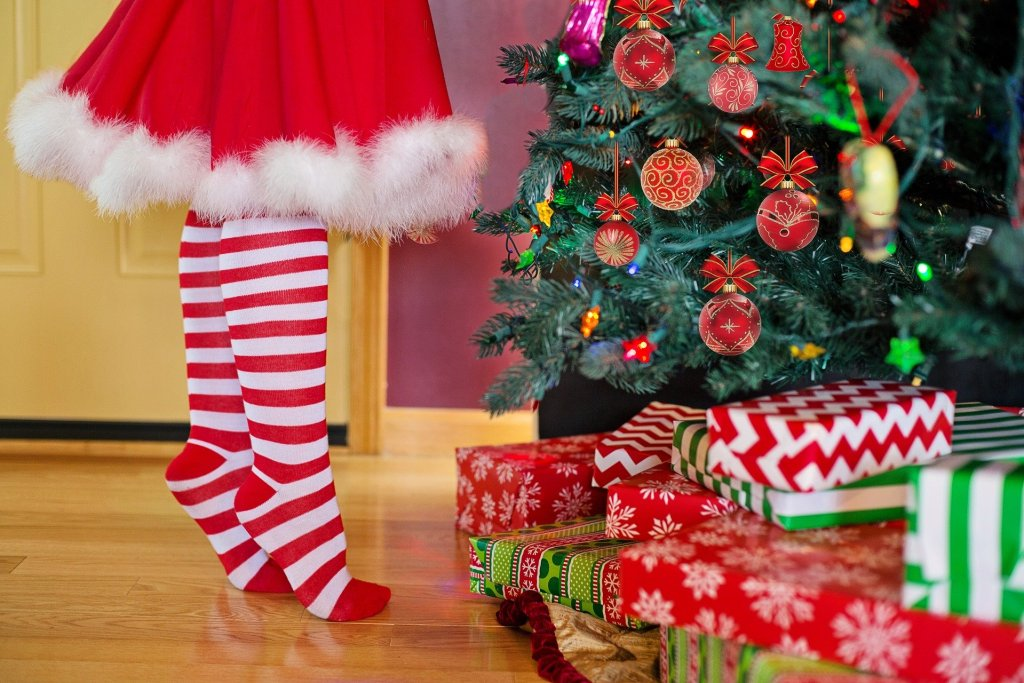 a child in red dress decorates Christmas tree - holiday budget