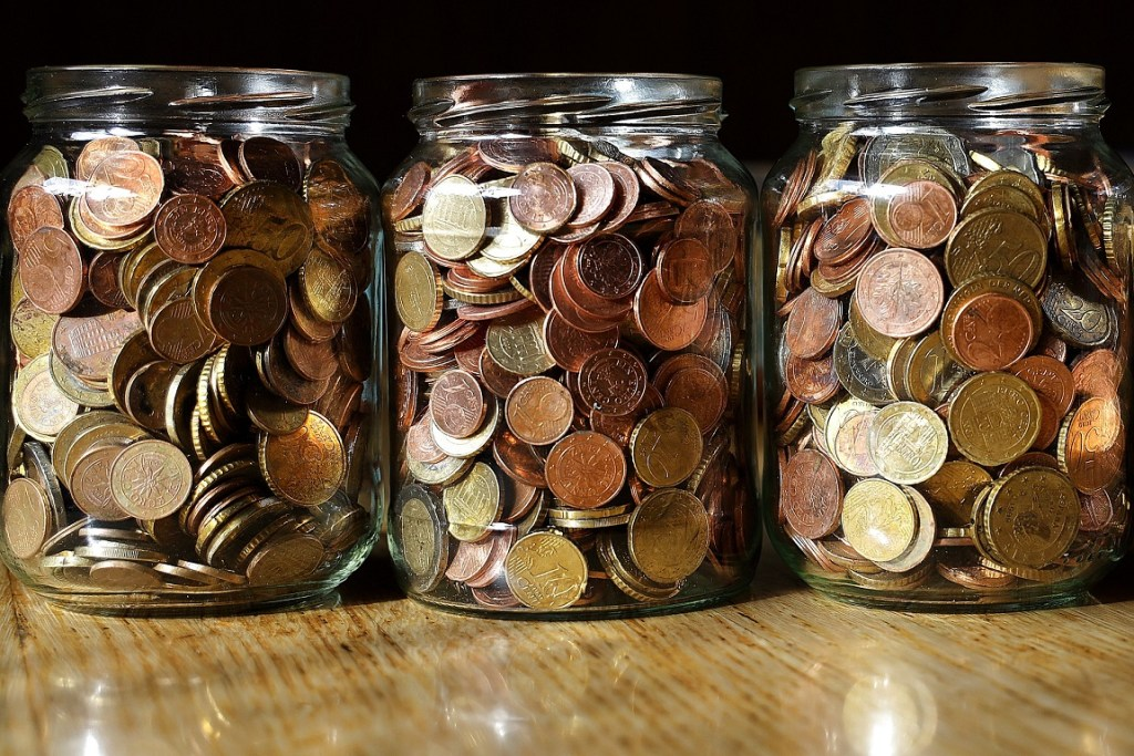 3 glass jars with coins - travel budget for retirement