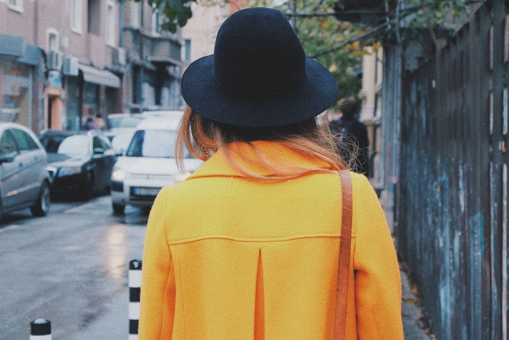 a woman in yellow coat walking a street