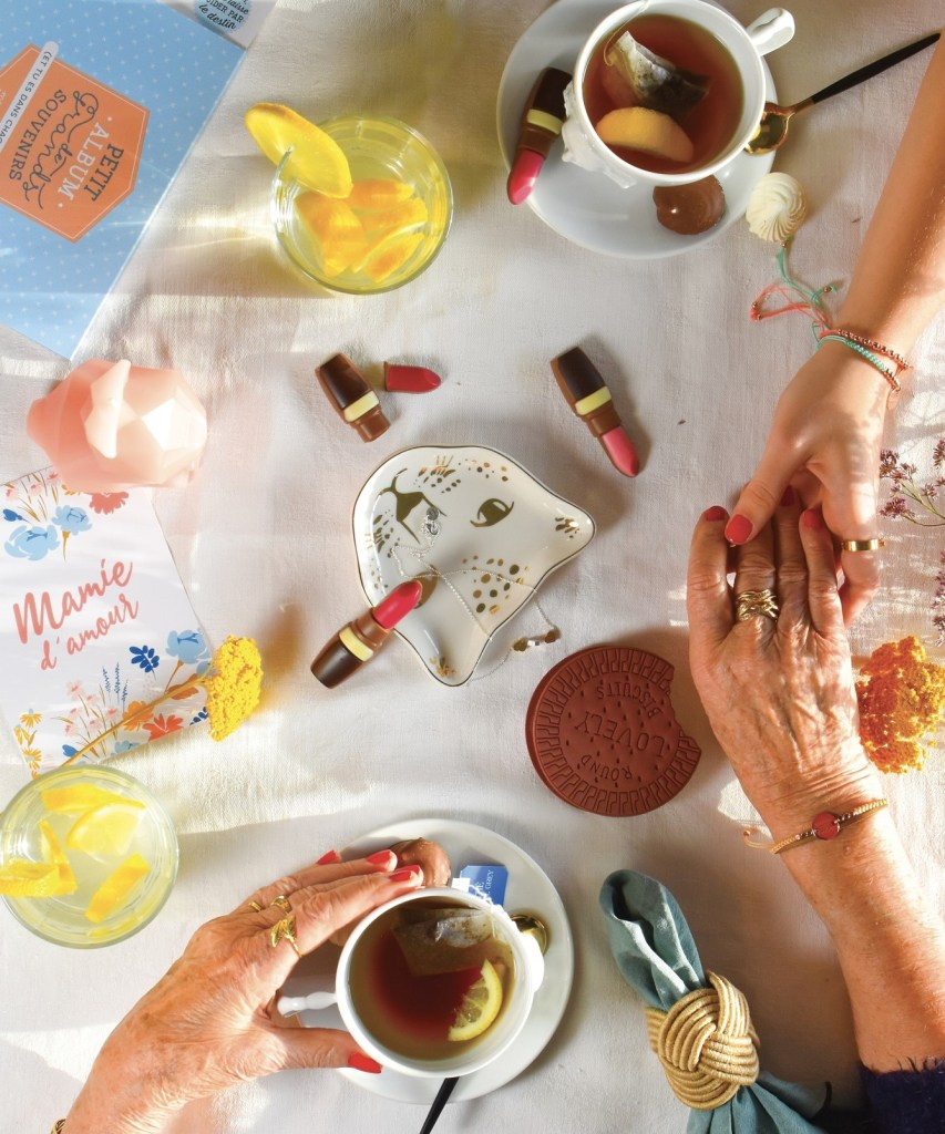 table with tea cups, lipstick and young and old women hands