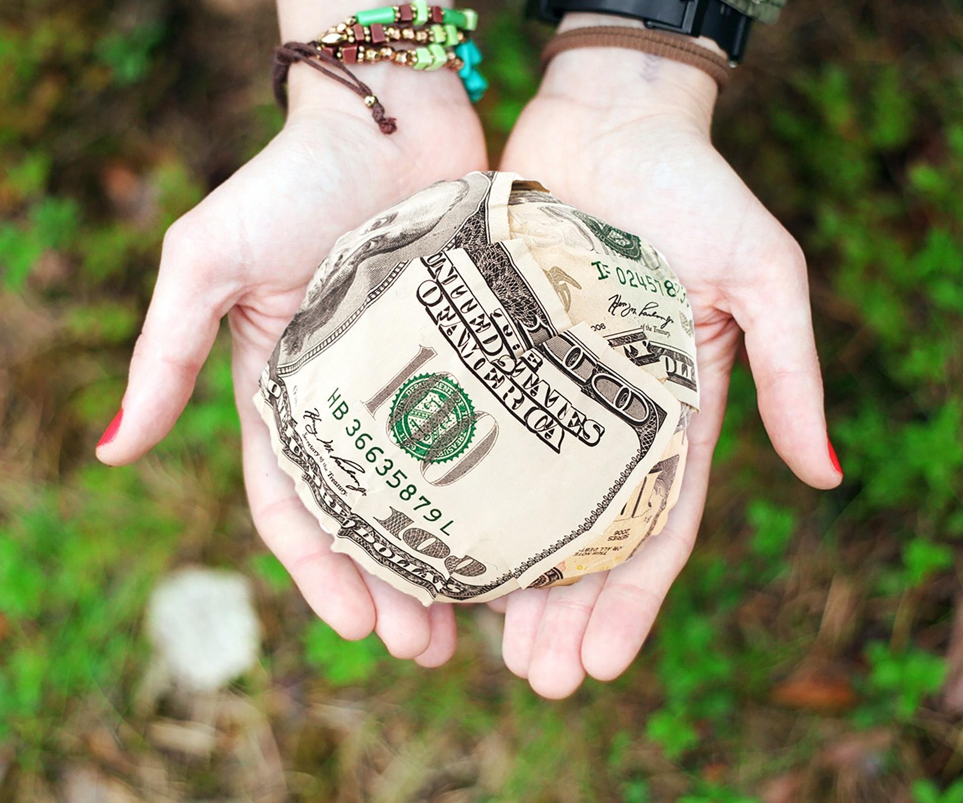 woman's hands - dollar bill - organize-simplify-your-finances