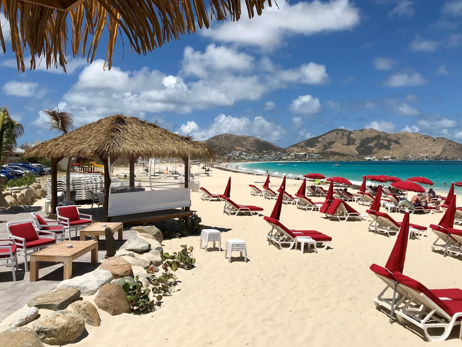 ocean beach with red umbrellas - retirement travel tips