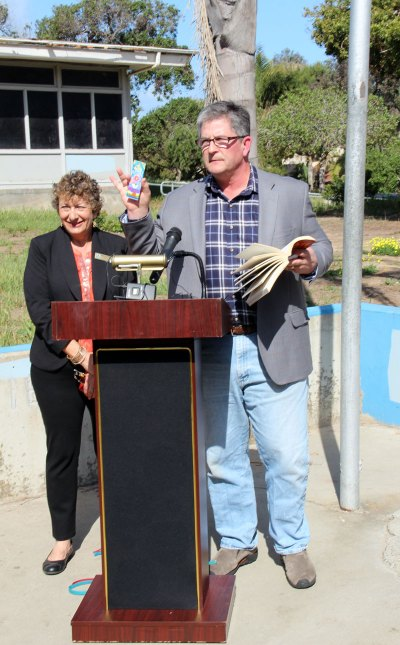 "At the March 27, 2014 joint press conference to announce the Pacific View purchase price, Councilmember Tony Kranz prepares to read ""The Road Not Taken"" by Robert Frost as School Board President Marla Strich looks on."