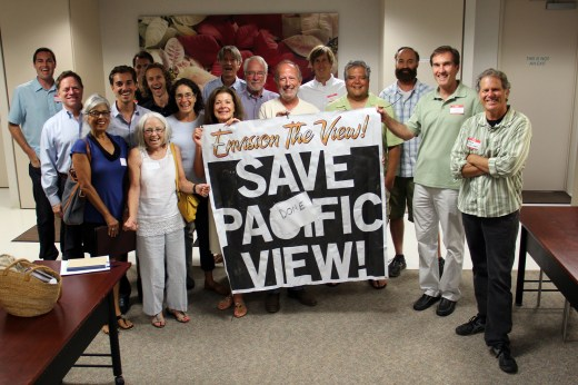 """Several Pacific View Collaboration Workshop participants gather around a banner from an earlier attempt to rescue Pacific View from development. Danny Salzhandler of the 101 Artists' Colony and the Arts Alive Foundation has triumphantly added a """"DONE"""" label to the banner."""