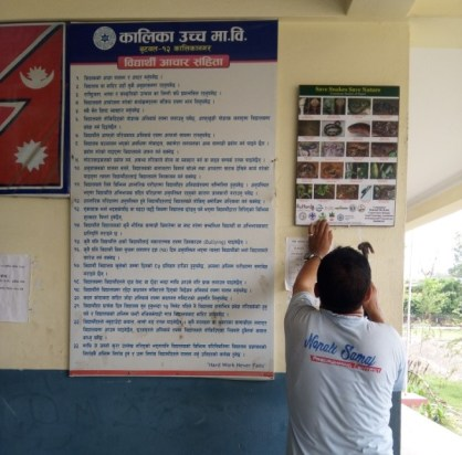 Schools staff hanging the Brochures and Posters on the notice board 1