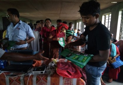 Jagadish Tharu distributing educational materials to the participants