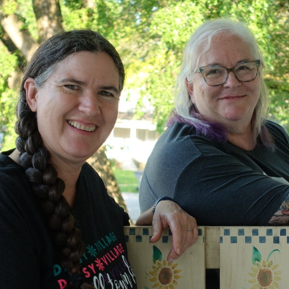 Becky McCray and Deb Brown on a front porch in a small town