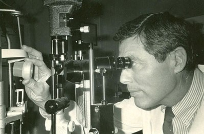 Physician viewing tissue through slit lamp.