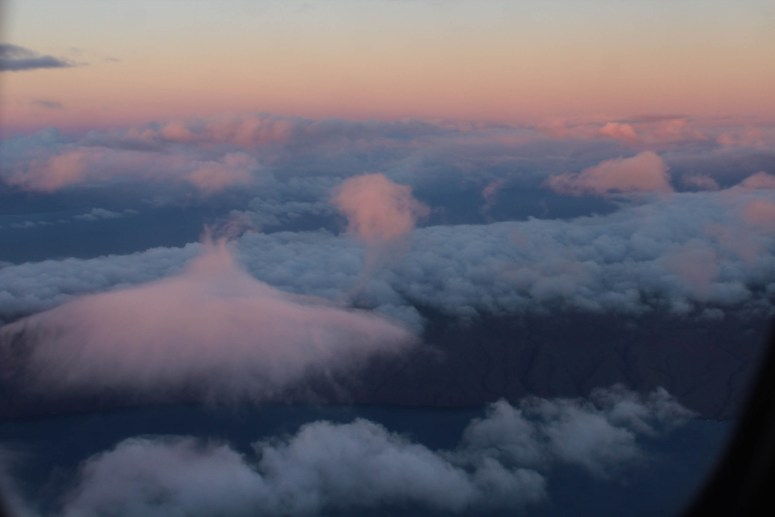 view outside plane window looking down on island and clouds during sunset